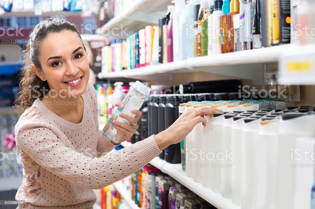 Garota escolher Amaciador de cabelo na loja - foto de acervo