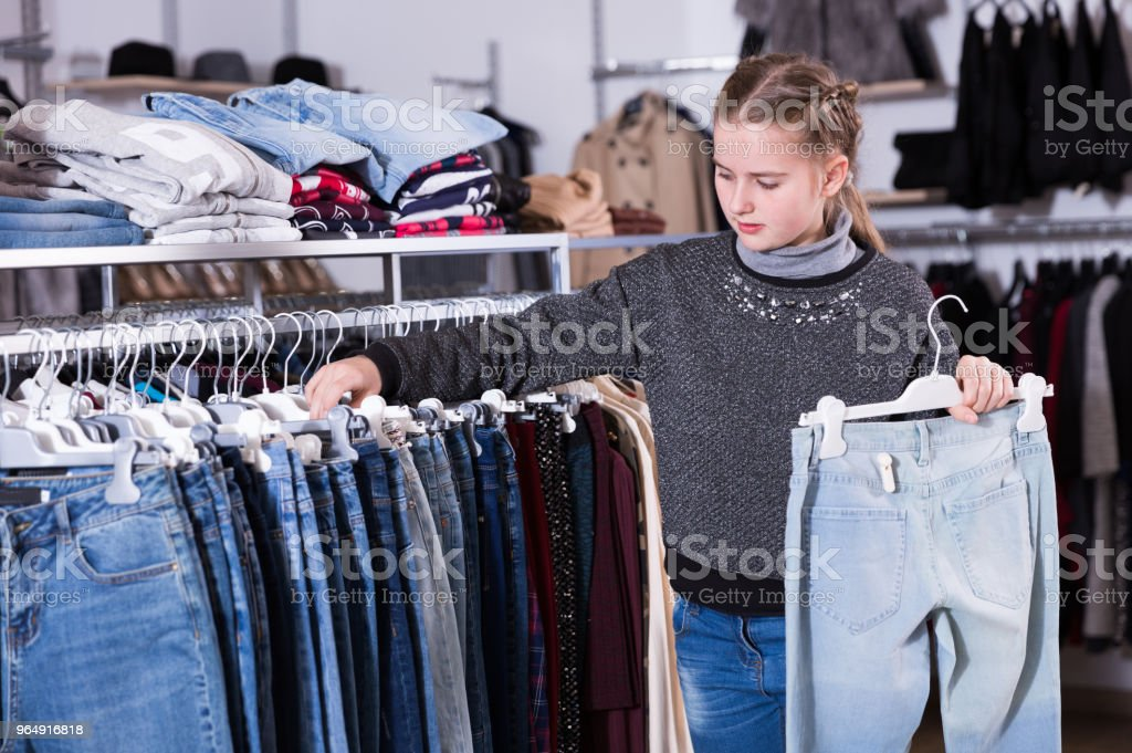 Girl choosing jeans in store royalty-free stock photo