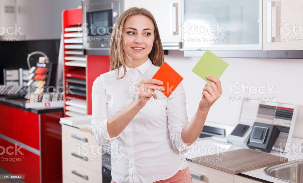 Girl choosing kitchen furniture materials stock photo