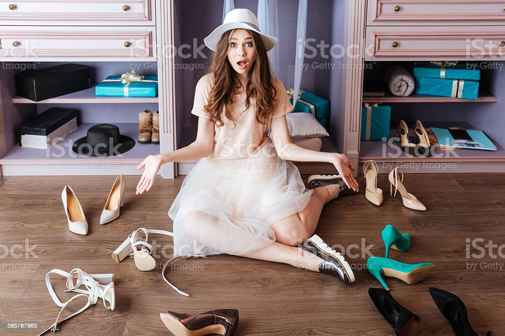 Girl choosing shoes in her wardrobe stock photo