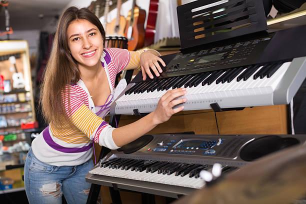 mädchen sie synthesizer im speichern - klavier verkaufen stock-fotos und bilder