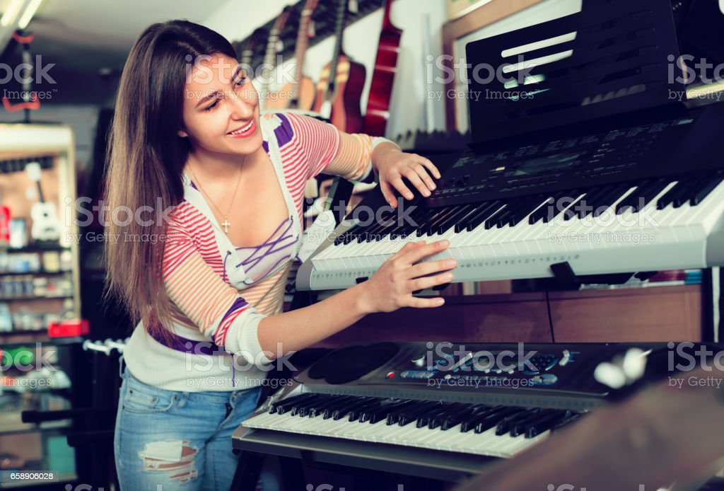 Girl Choosing Synthesizer In Store Stock Photo & More