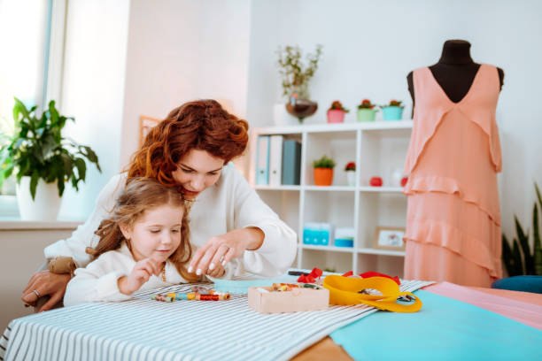 Girl choosing thread while working in atelier with mom stock photo