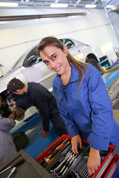 Girl choosing tools to repair car in garage stock photo
