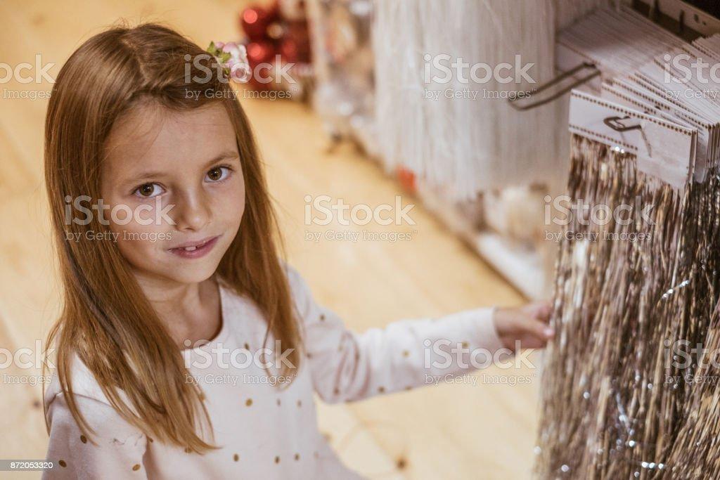 Girl chosing christmas decoration in christmas market stock photo
