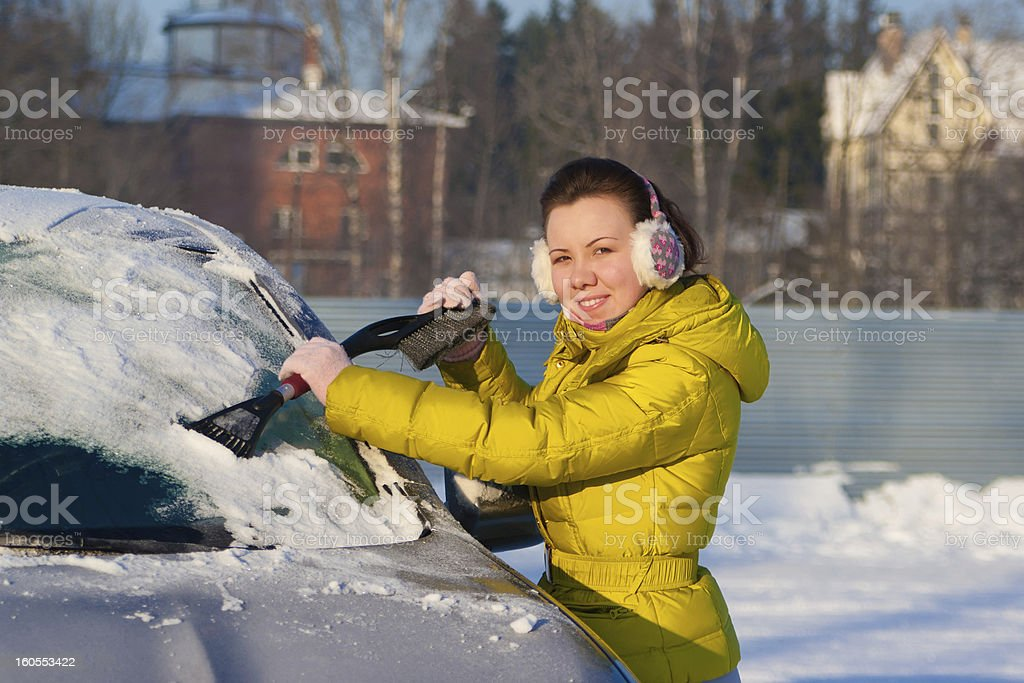 Girl cleaning car from snow stock photo