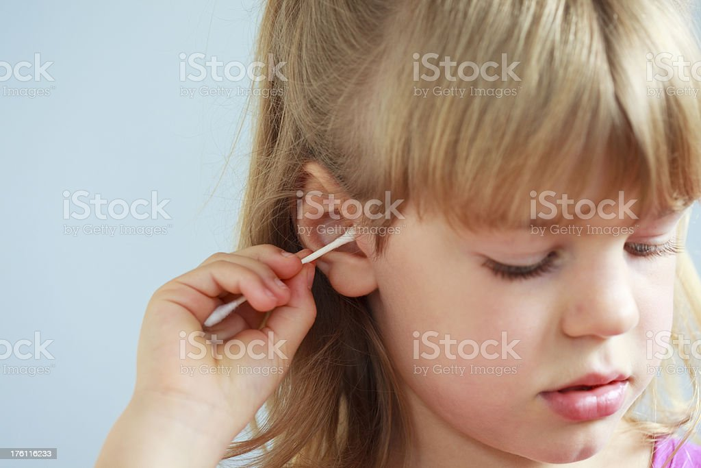 Girl cleaning ear with Q-tip stock photo