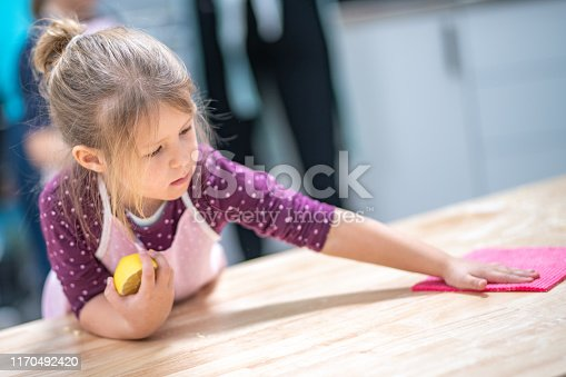 Girl cleaning table with a sponge in cooking class.