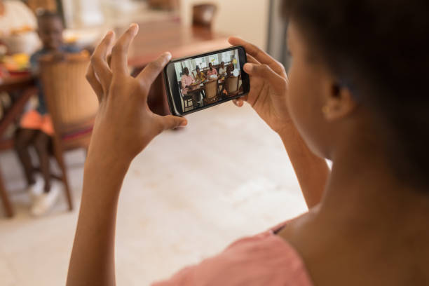Girl clicking photos of family with mobile phone on dining table stock photo