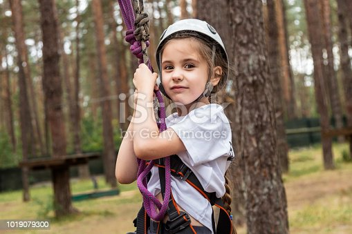istock Girl climber hanging on insurance in the forest 1019079300