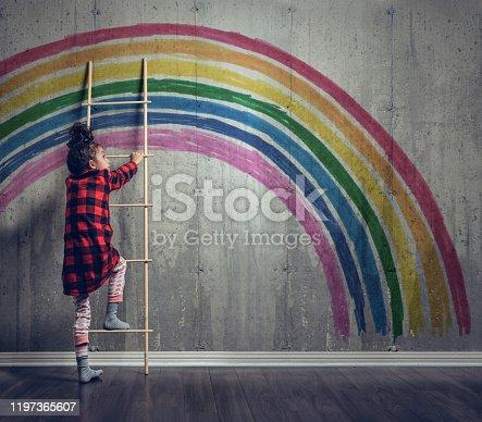 Girl climbing to reach the rainbow