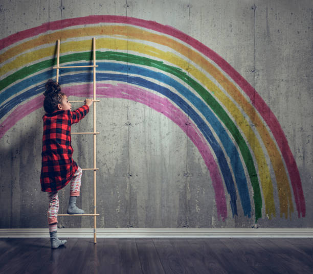 Girl climbing to reach the rainbow stock photo