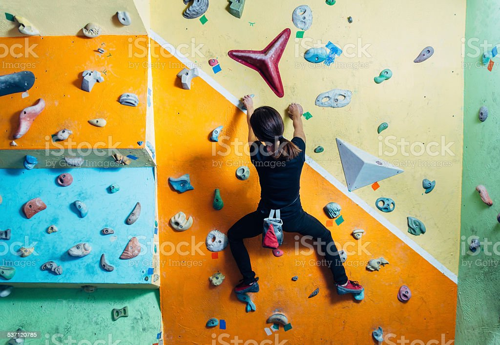 Girl climbing up on wall indoor stock photo