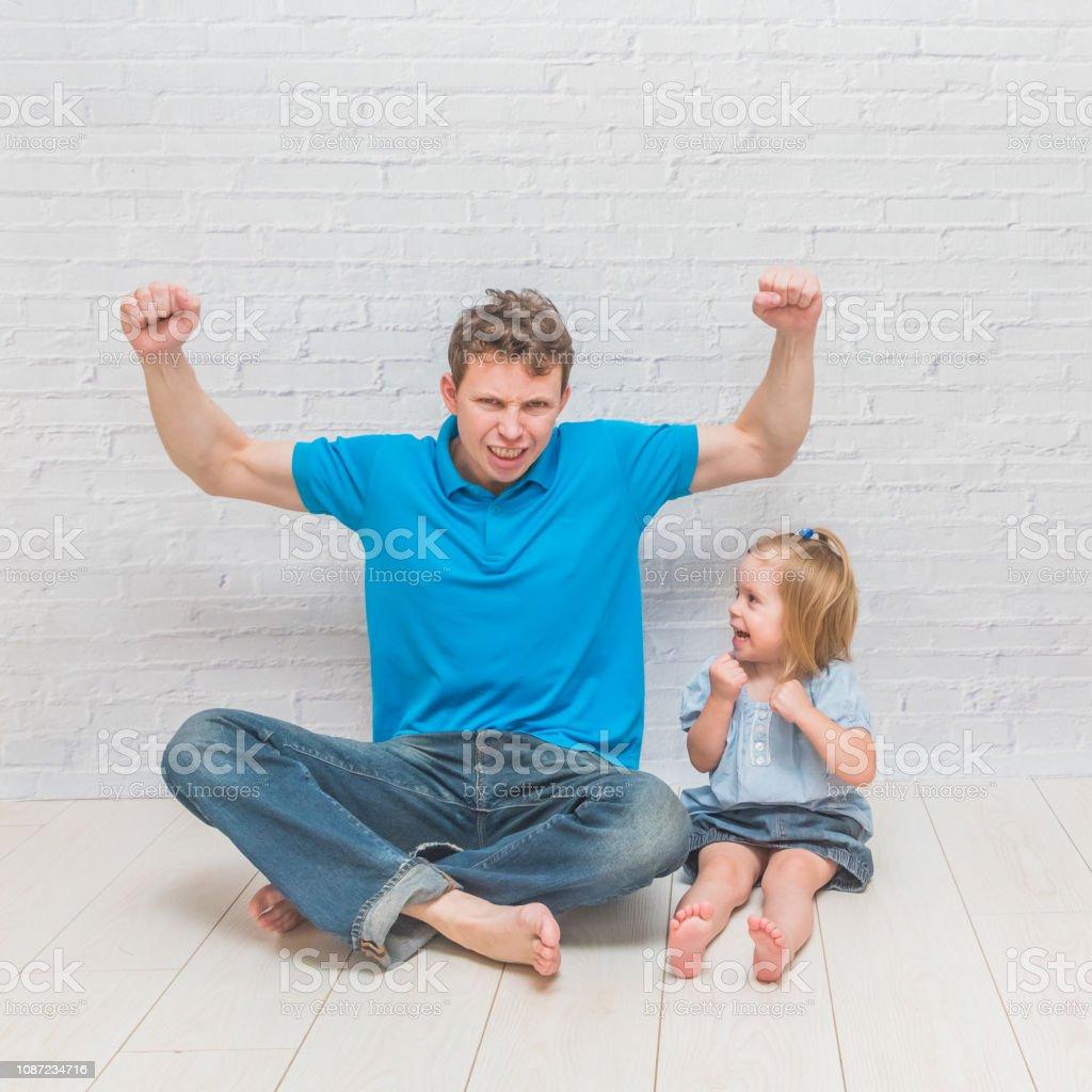 garota sobe, brincar com o pai em uma parede de tijolos brancos - foto de acervo