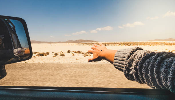 Girl close up hand playing with the wind like a wing outside the car traveling for alterntive vacation with desert and mountains outdoors view - holiday summer car travel tourism concept stock photo