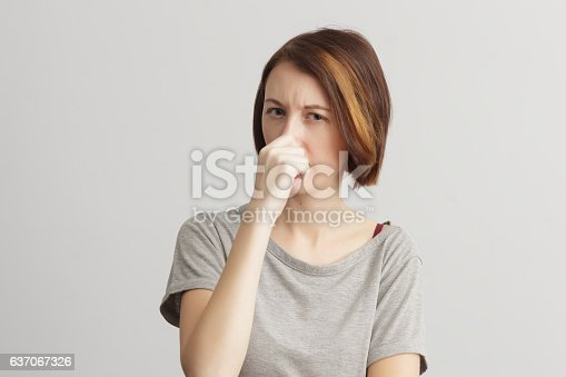 istock Girl closes her nose because of the odor and stench. 637067326