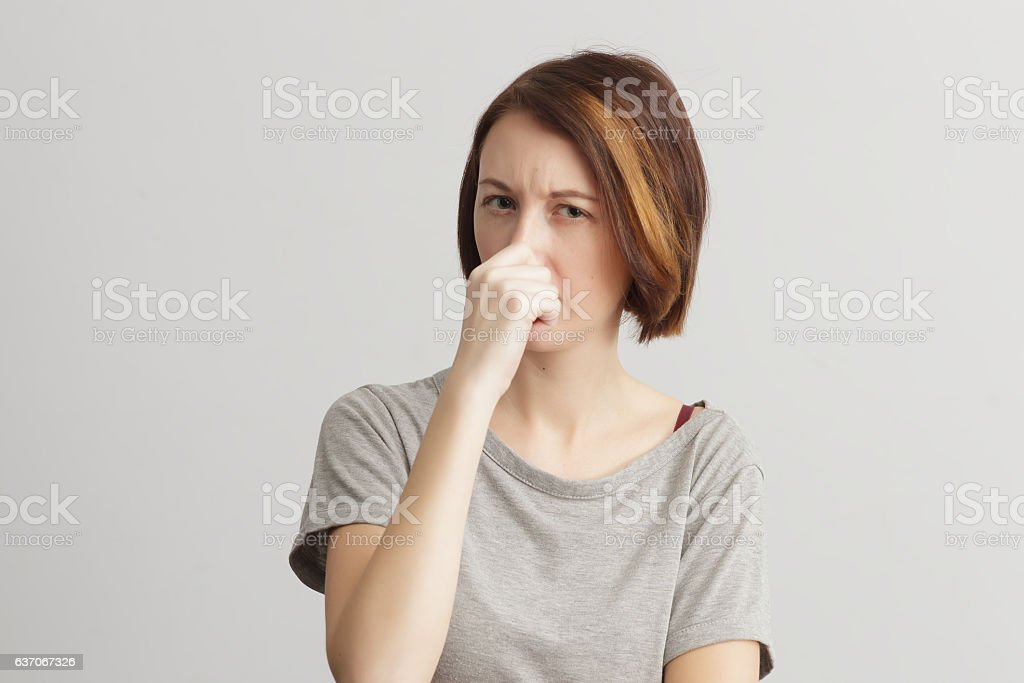 Girl closes her nose because of the odor and stench. stock photo