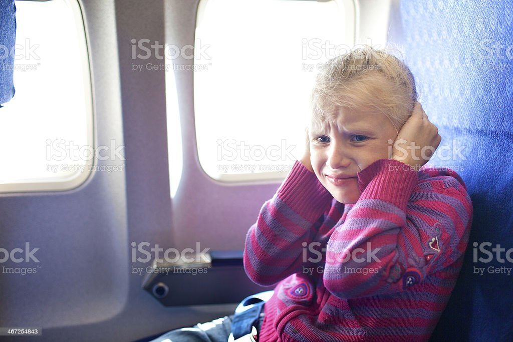 girl closing ears in the airplane stock photo