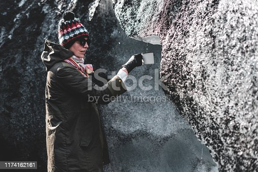 Girl in a khaki jacket surrounded by ice and black sand from the glacier. She hold white metal mug in hands.