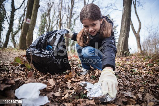 Young girl volunteering and collecting trash in nature