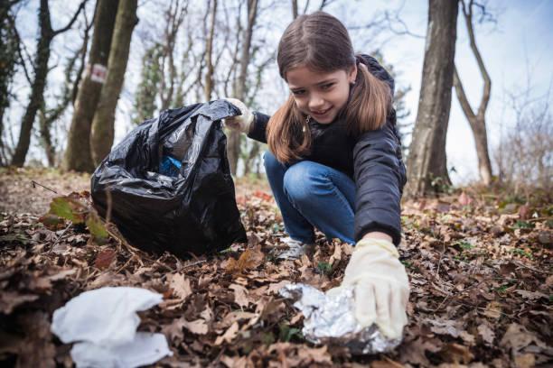 ragazza che raccoglie rifiuti nei boschi - ambientalista foto e immagini stock
