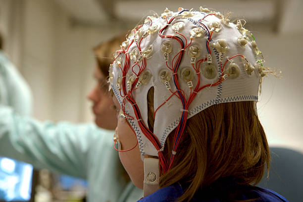 girl connected with cables for EEG for a scientific experiment stock photo
