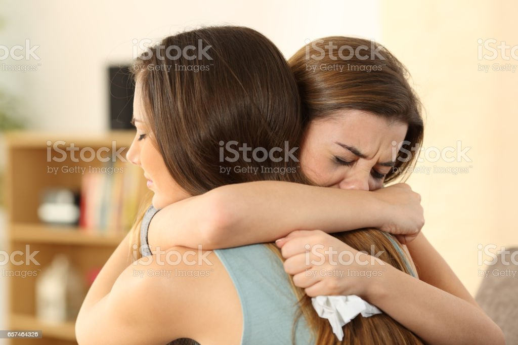 Girl consoling to her sad best friend stock photo