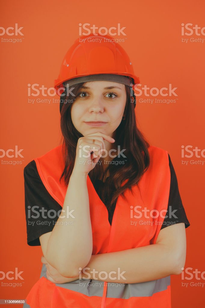 a woman in a helmet and orange vest