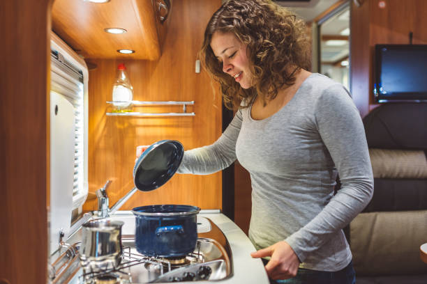 Girl cooking in a caravan Girl cooking in a caravan, motorhome rv interior stock pictures, royalty-free photos & images