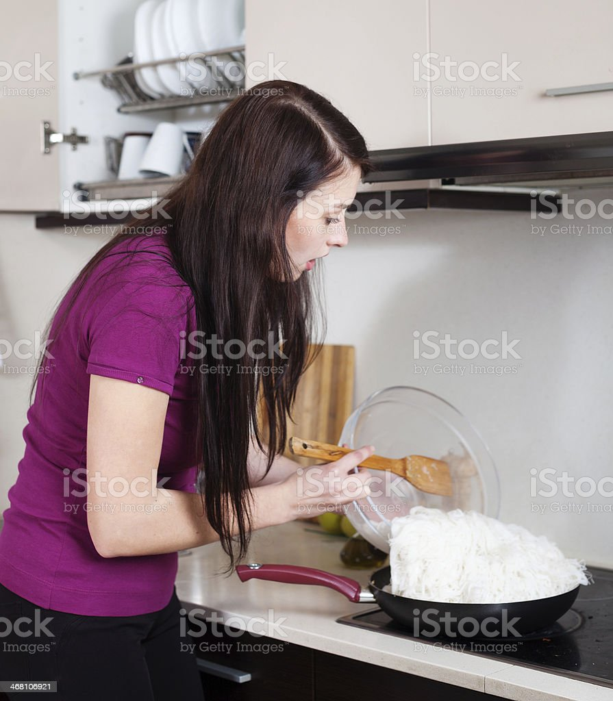 girl cooking rice noodles in skillet royalty-free stock photo