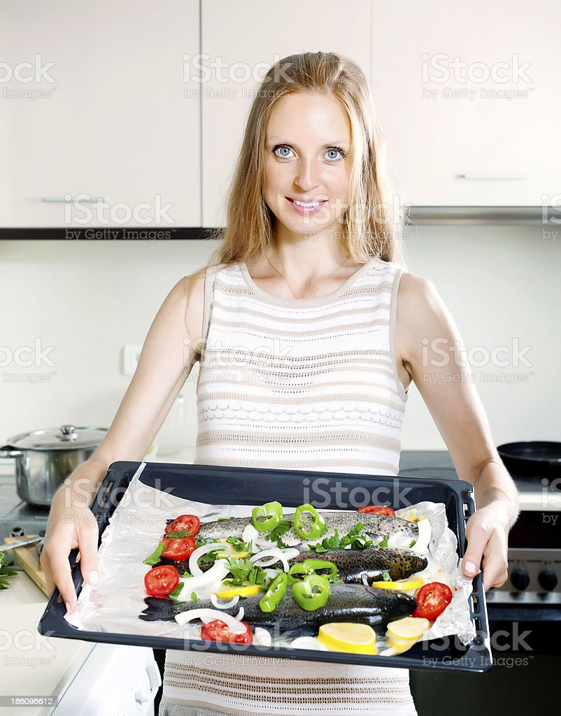 girl cooking trout fish in pan royalty-free stock photo
