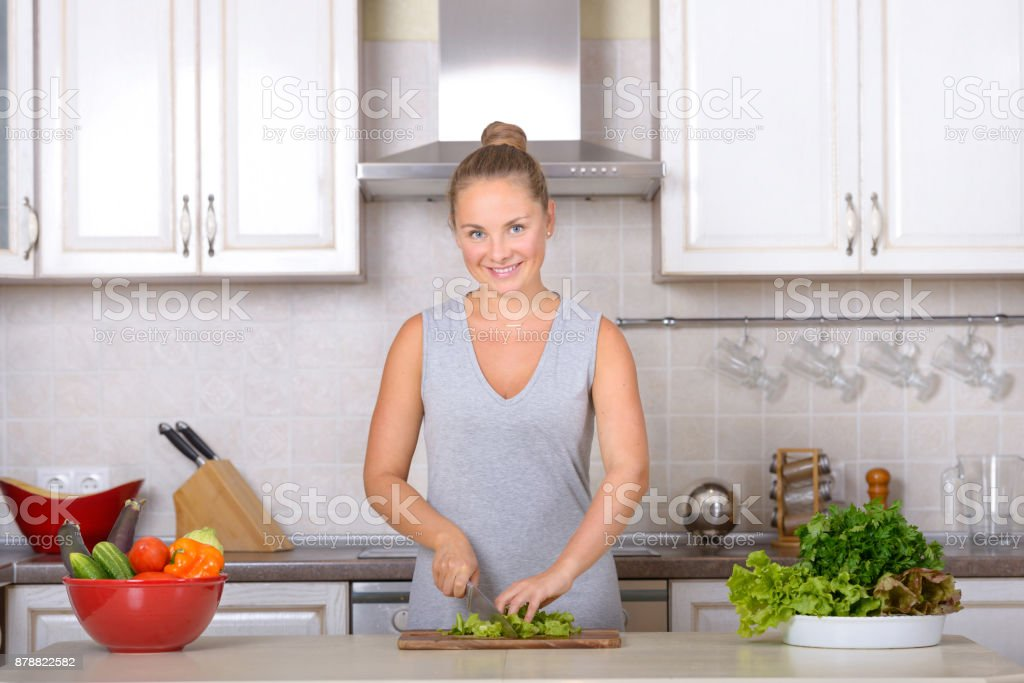 Girl cooking vegetarian salad in kitchen stock photo