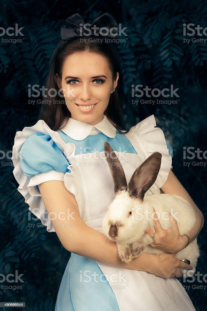 Girl Costumed como Alice in Wonderland con el conejo blanco - foto de stock