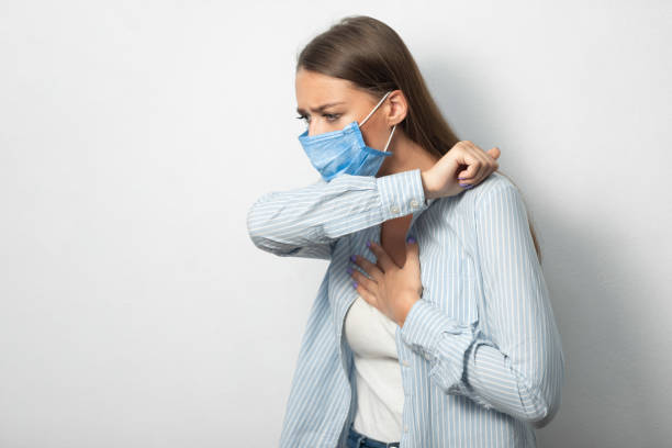 Girl Coughing Into Elbow Wearing Mask Standing Over White Background stock photo