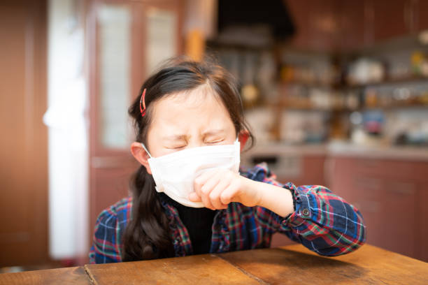 Girl coughing wearing a mask stock photo