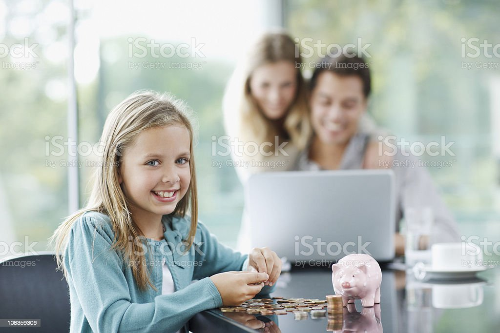 Girl counting coins with parents in background stock photo