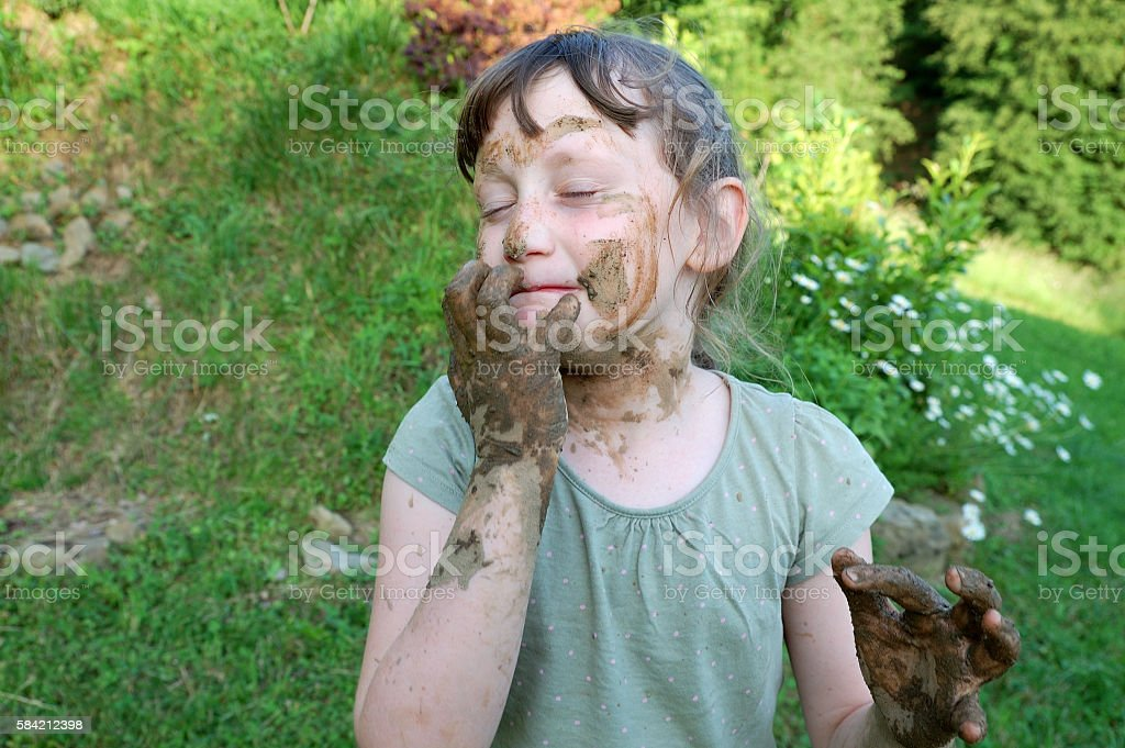 girl covered with mud stock photo
