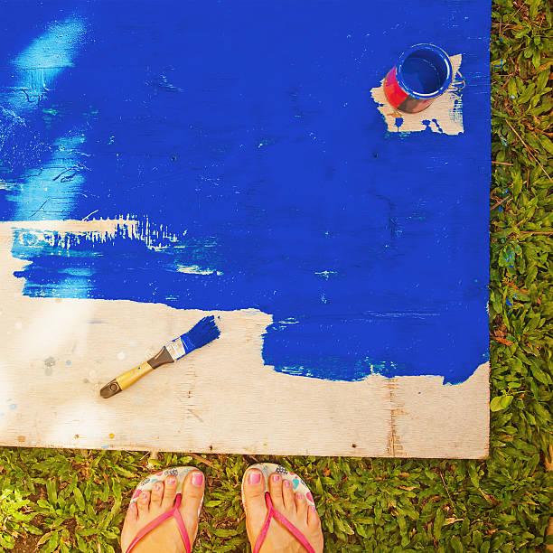 mädchen auf einem holz-board mit blaue farbe (gesicht - flip flops reparieren stock-fotos und bilder