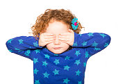 Little girl covering her eyes; isolated on white.