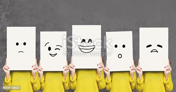 Emotions set. Girl hiding face behind signboard with drawn smileys. Collage of indifferent, winking, happy, surprised, and sad emoticons.