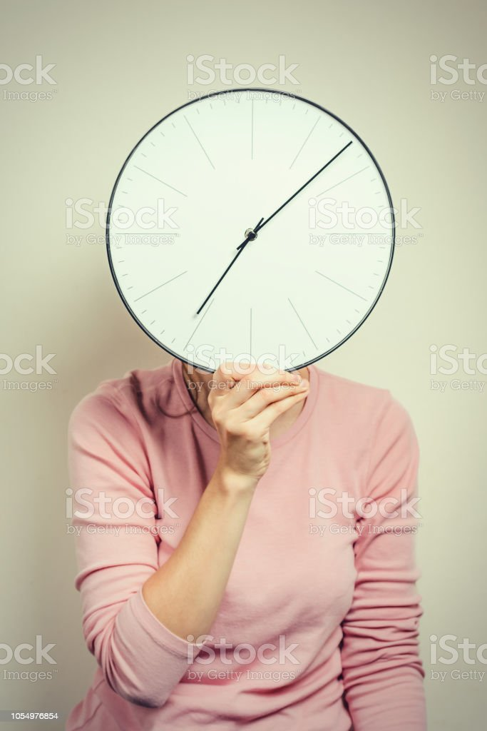 Girl covering her face from clock. Woman hides from stress and...