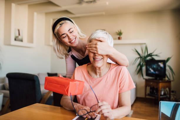 dziewczyna zakrywająca oczy matki i dająca jej prezent - gift zdjęcia i obrazy z banku zdjęć