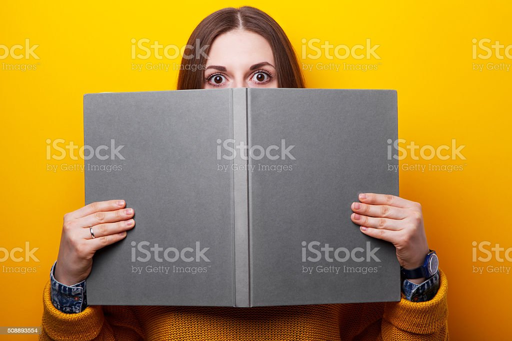 Girl covers her face with a book stock photo