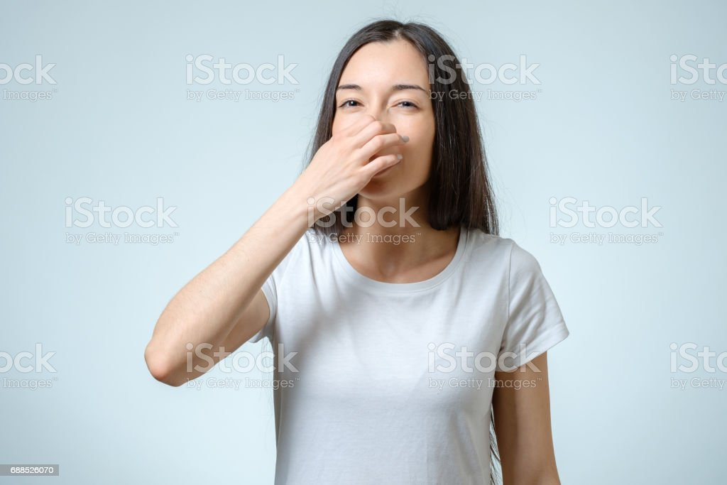 Girl covers nose with hand showing that something stinks isolated on gray background stock photo