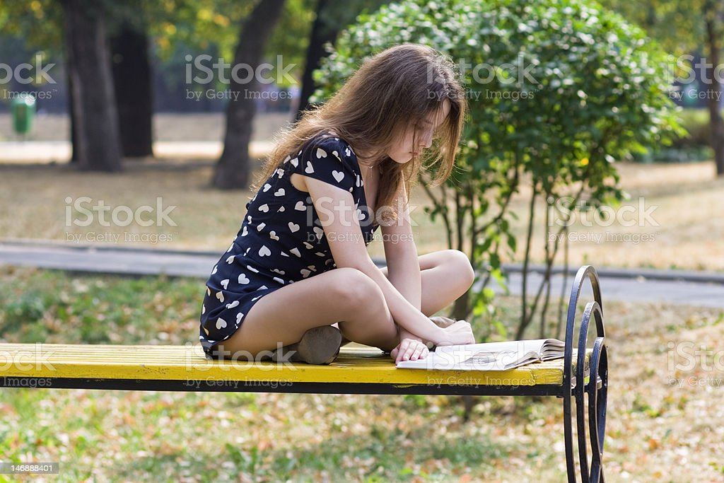 Girl crossed legs sitting on bench in park reading book. stock photo