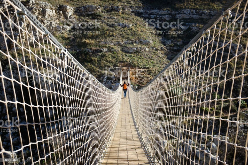 Girl crosses the rope bridge in the Matera canyon - foto stock