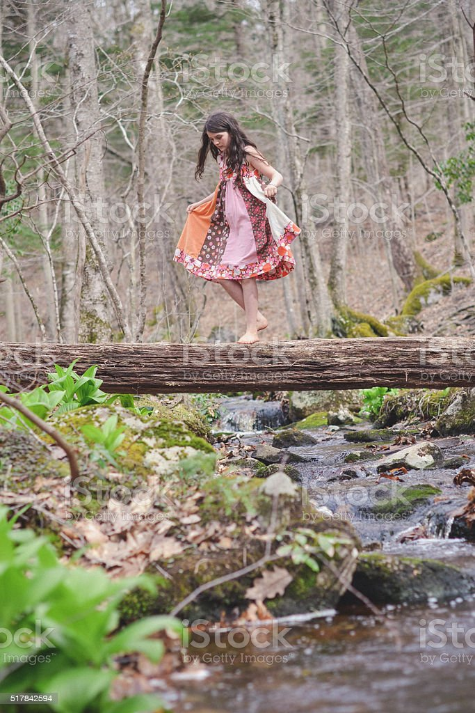 Girl crossing a fallen tree branch over a stream in a dress stock photo