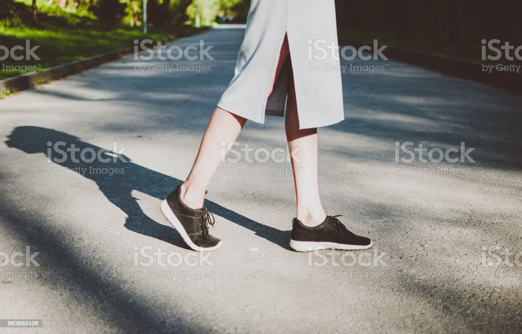Girl crossing road and her figure casting deep dark shadow. - Royalty-free Adult Stock Photo