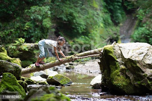 Girl crossing the log bridge