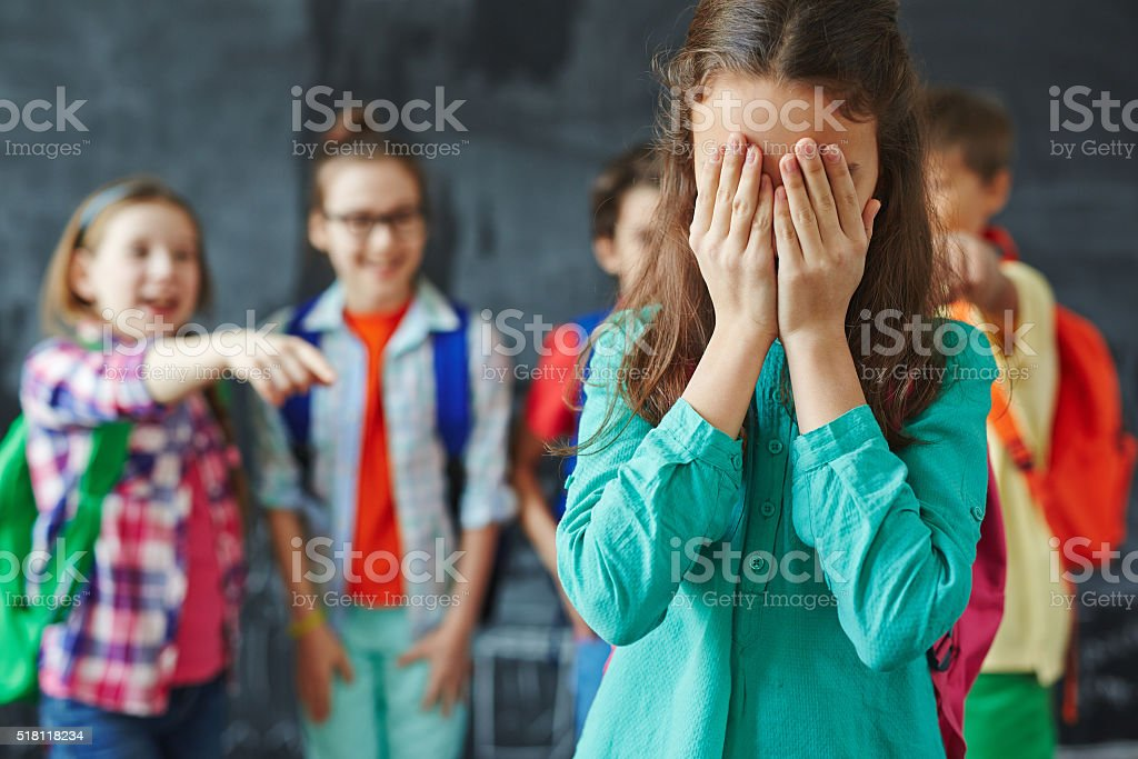 Girl crying Schoolgirl crying on background of classmates teasing her Bullying Stock Photo
